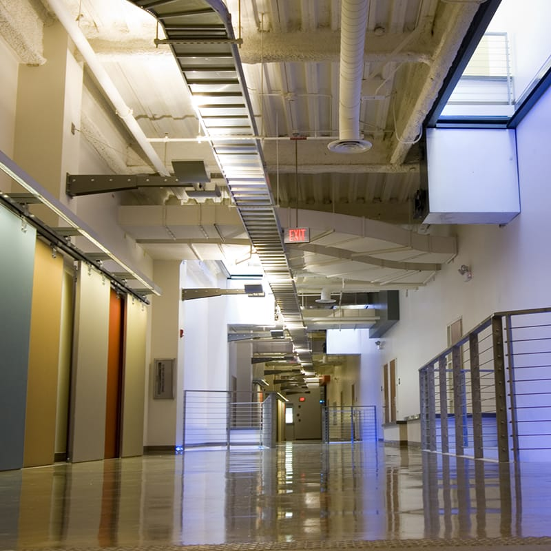 The finishes include stained concrete floors, wood paneling at the elevator cores in the entry lobby, sliding bulletin