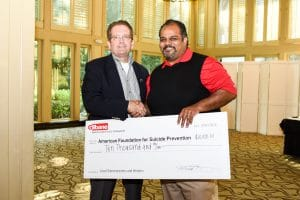 Michael Brown, senior vice president Gilbane Building Company, presents Roland J. Behm, Chair, Board of Directors of American Foundation for Suicide Prevention Georgia Chapter with a donation