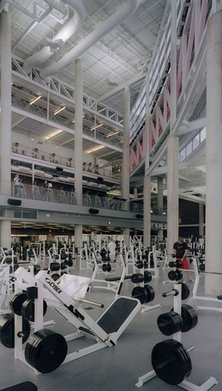 Weight room interior includes exposed steel and architectural and stained concrete pillars